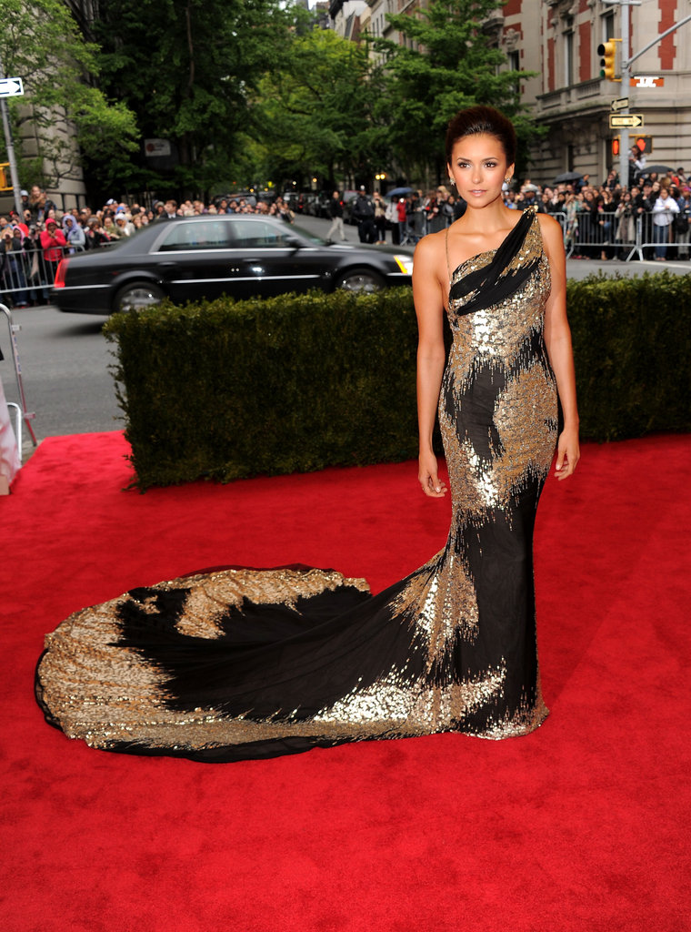 Nina Dobrev attended the 2012 Met Gala in an eye-catching liquid black-and-gold Donna Karan Atelier gown — just look at that train!