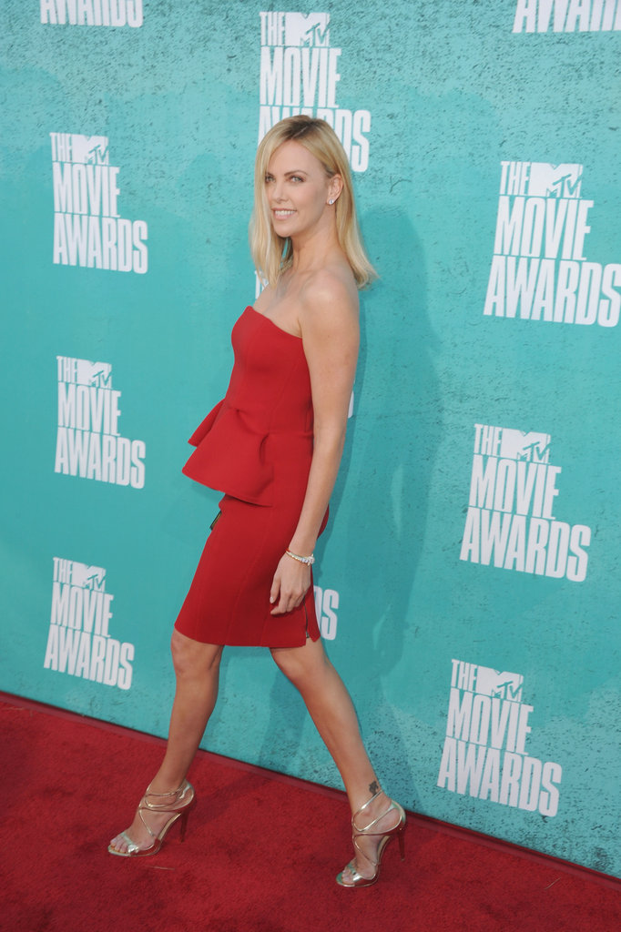 Charlize Theron strut onto the carpet in high silver heels.