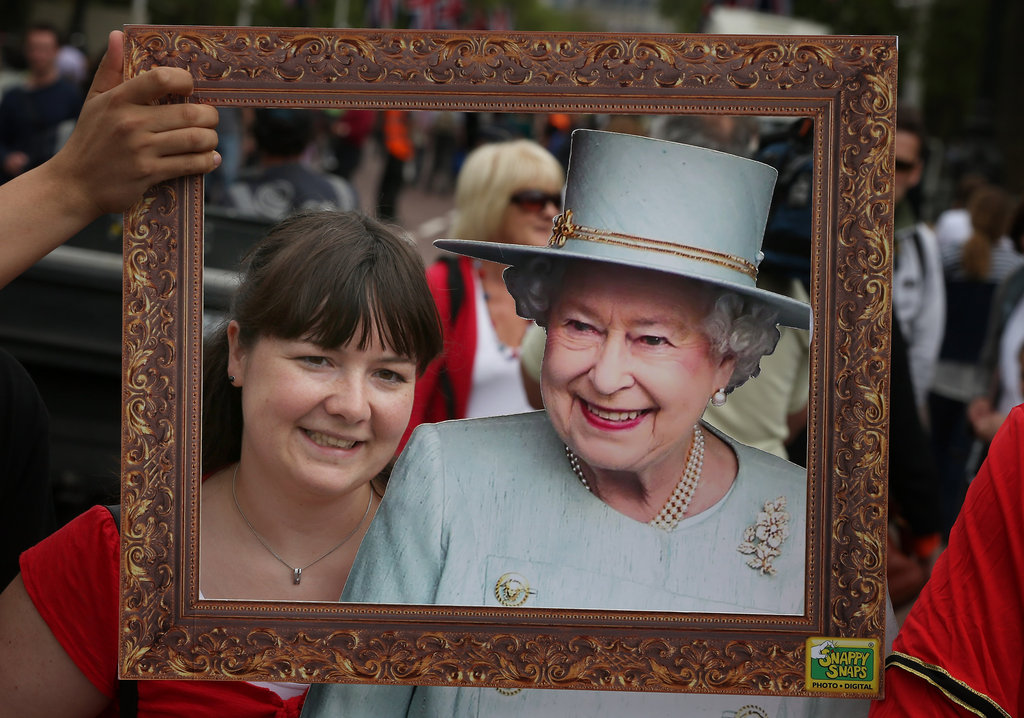 A woman posed with a cardboard cutout of Queen Elizabeth.
