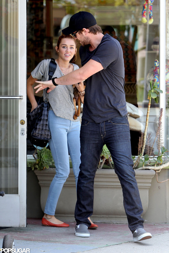 Liam Hemsworth held the door for Miley Cyrus while shopping for their new puppy in LA in May 2012.