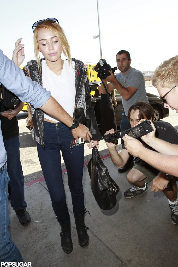 Miley Cyrus caught a flight at LAX wearing her new engagement ring.