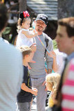 David Beckham held Harper Beckham who wore Minnie Mouse ears at Disneyland.