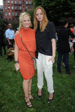Amy Poehler wore a bright orange dress and posed with Stella McCartney at her Spring presentation in NYC.