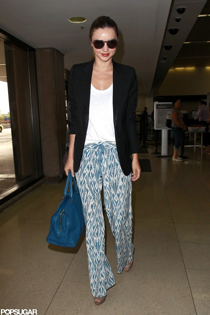 Miranda Kerr walked through the airport in cute printed pants and a matching blue bag.