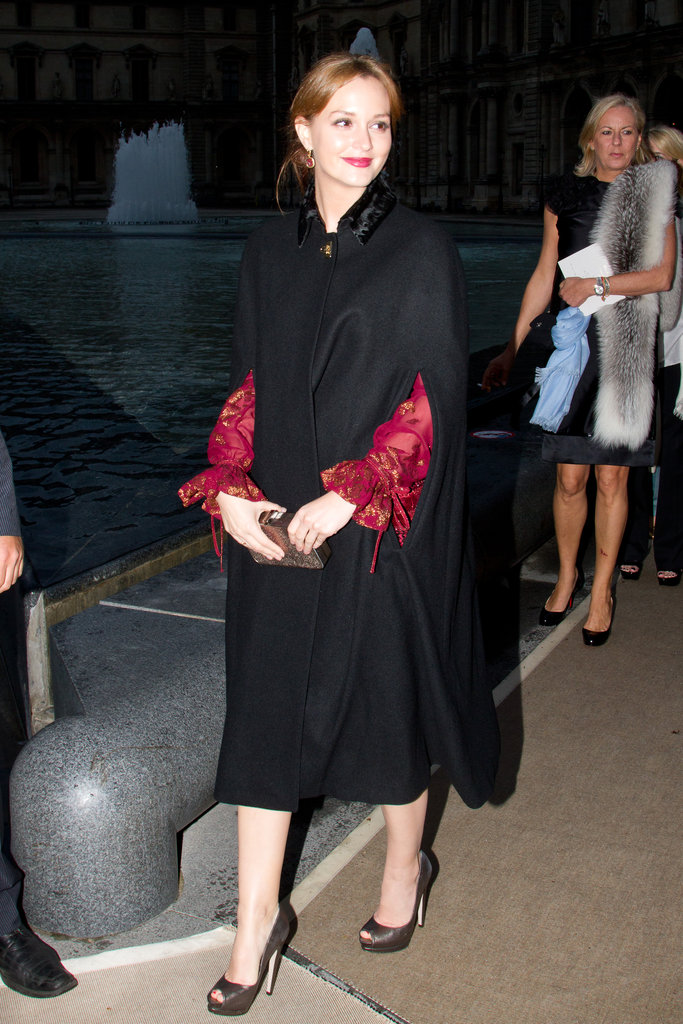 Leighton Meester arrived at the Salvatore Ferragamo Resort collection show in Paris wearing a black cape over her dress.