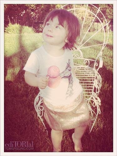 Stella's chic cousin Simone, aka the Guncles' daughter, sitting casually in a sequin skirt, eating a cake pop. Girls just wanna have fun!