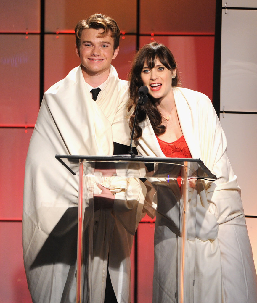 Zooey Deschanel and Chris Colfer wrapped themselves in white sheets to take the stage at the Critics' Choice Television Awards in LA.