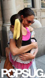 Suri Cruise wore a yellow ribbon in her hair as she clutched onto mom Katie Holmes in NYC.