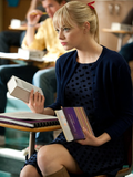Gwen studying in a black-and-navy polka-dot dress, navy cardigan, tan boots, and a red ribbon in her hair.  7338158