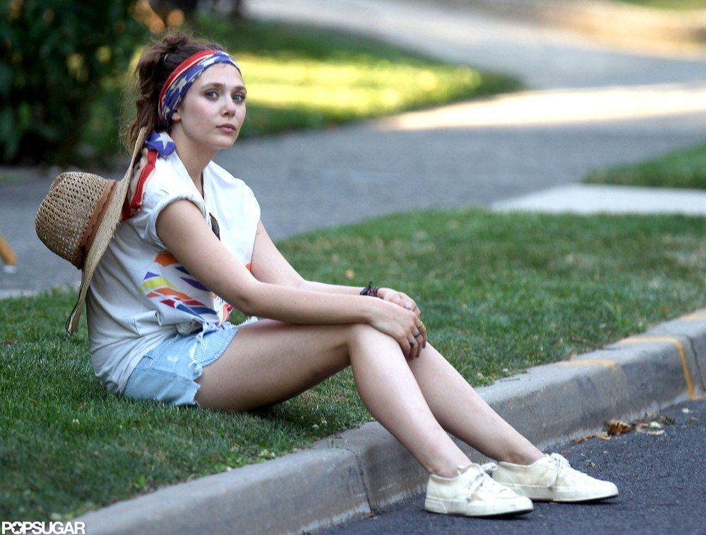 Elizabeth Olsen relaxed in the grass on set.