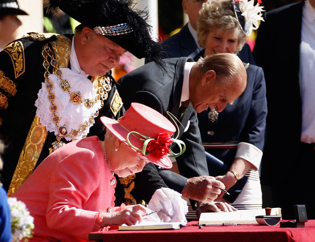 The queen and the Duke of Edinburgh sign the visitors' book at Birmingham's Victoria Square.