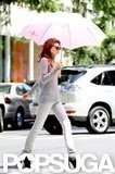 Miranda Kerr crossed the street carrying an umbrella during the photo shoot.