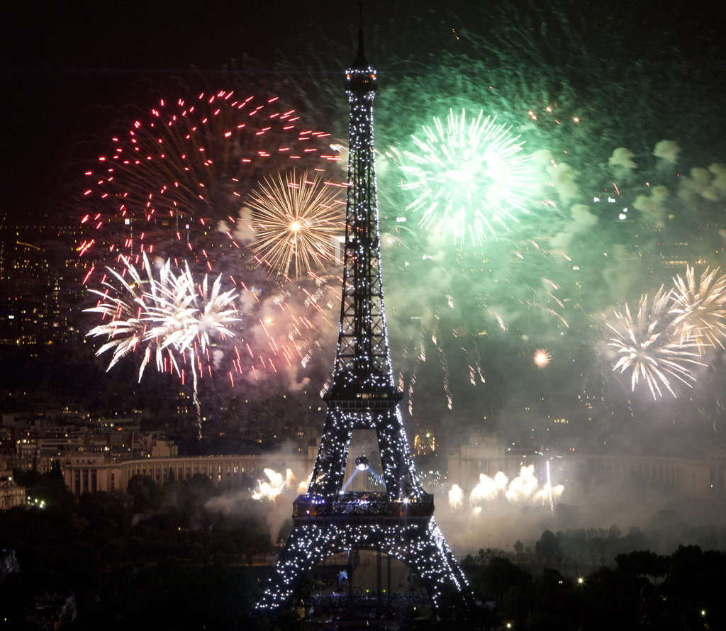 Brightly colored Bastille Day fireworks lit up beside the Eiffel Tower.