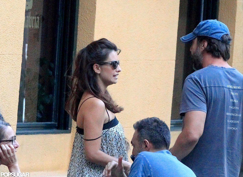 Penelope Cruz and Javier Bardem stood to leave the outdoor café.