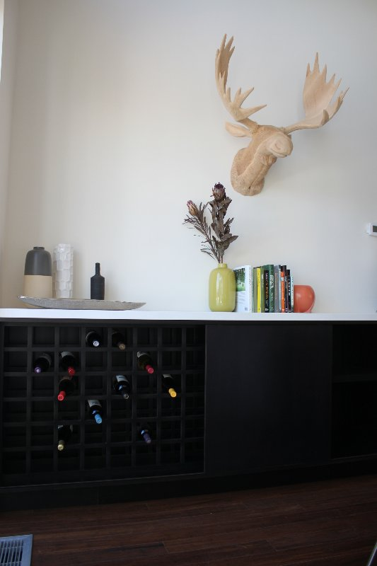 Another built-in cabinet features plentiful storage for wine as well as cabinets. The wooden moose head is from Roost.