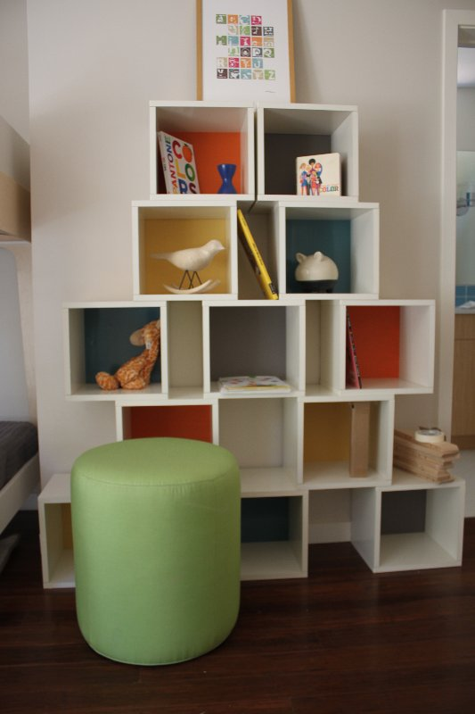 Simple cubes were painted with pops of color and stacked to create this modular shelving unit. It's an easy DIY you could try at home.