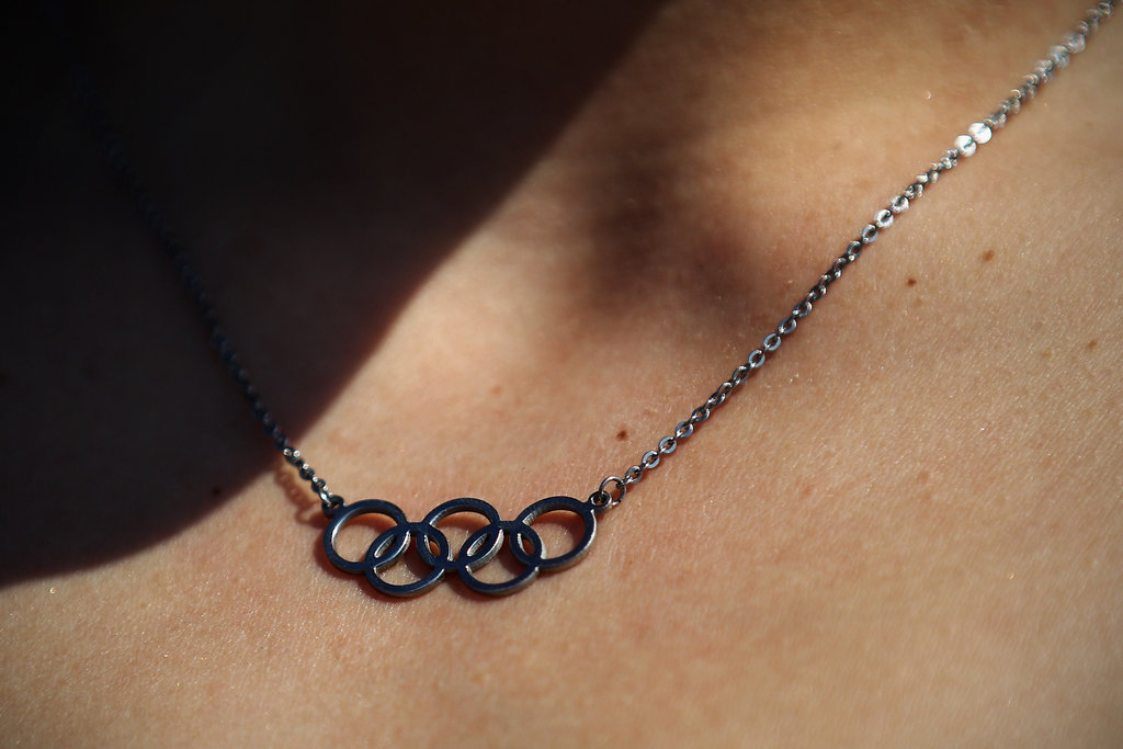A woman wore a necklace with the Olympic rings on it.