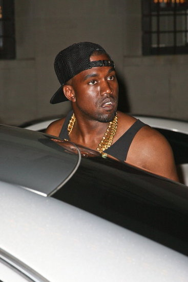 Kanye West wore gold chains and a baseball cap.