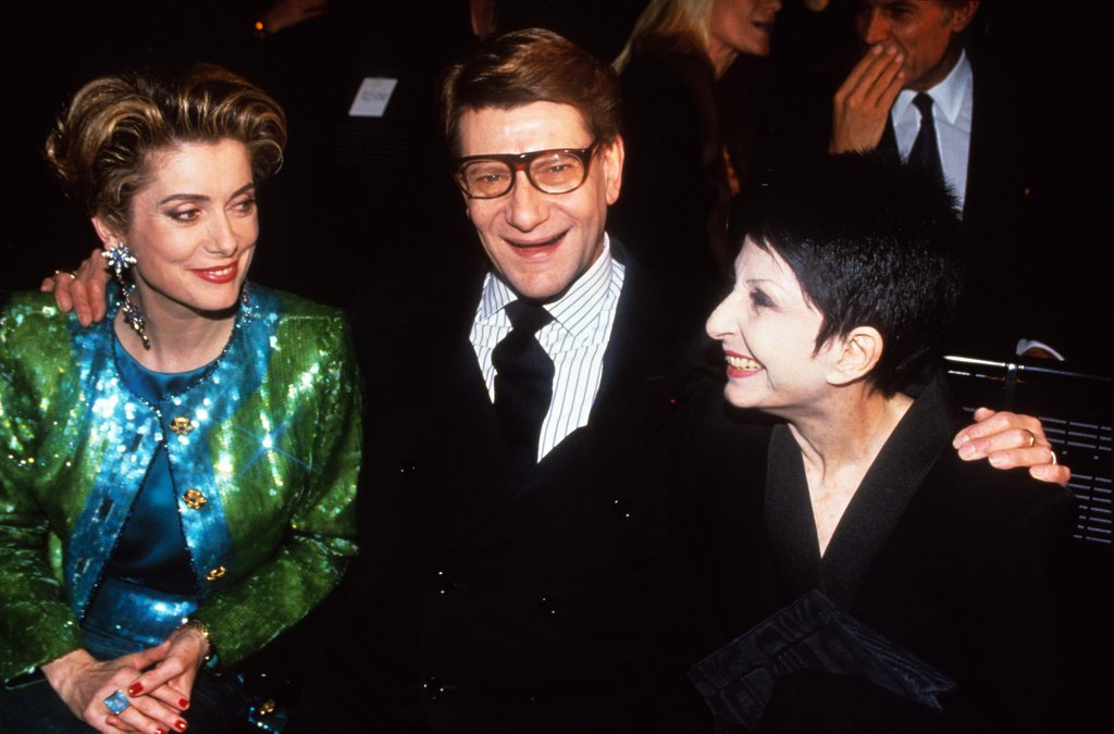 The designer sat between a dressed-up Catherine Deneuve and Zizi Jeanmaire in 1988.