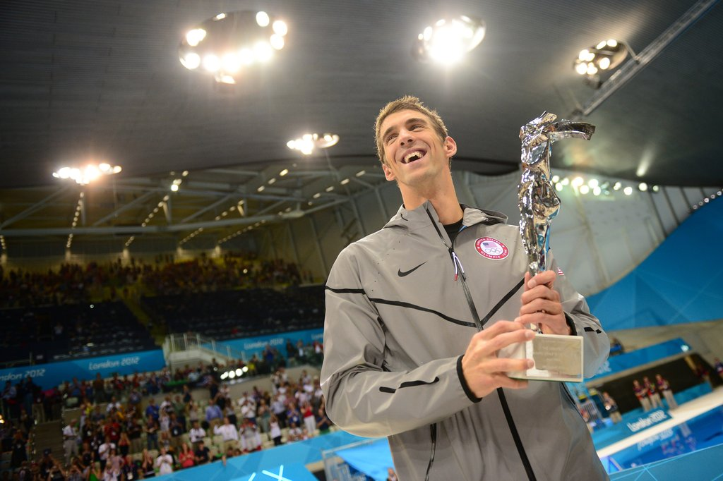 After winning the 4x100m medley relay, Michael Phelps received a trophy for being the greatest Olympian of all time. Michael's total medal count during his career is 22, 18 of which are gold medals.