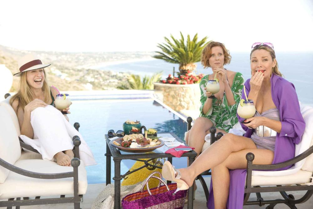 Poolside for Samantha means lounging in heels, a shiny bathing suit, and a luxurious purple silk robe.