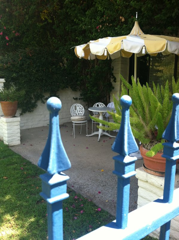 A peek over the blue iron gates reveals the love-themed garden seats and striped retro umbrellas belonging to the lanai rooms.