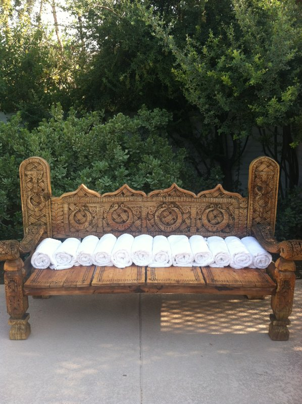 At the family-friendly North Pool, an intricately carved wooden bench holds fresh towels instead of people.