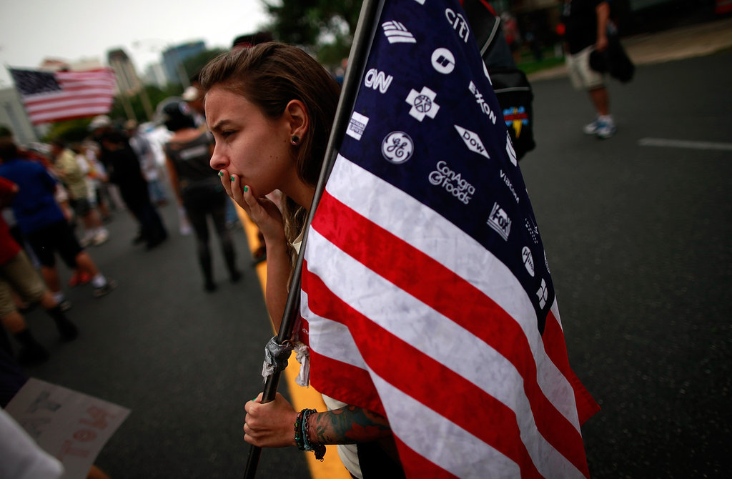 A woman held a flag in the streets outside the RNC.