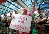 "A Code Pink protestor held a sign saying ""Condi war criminal."""