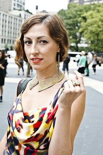 A curly, '20s-esque bob was brought to greater heights with a cat-eye liner, orange lipstick, and gold nail polish. Photo by Caroline Voagen Nelson