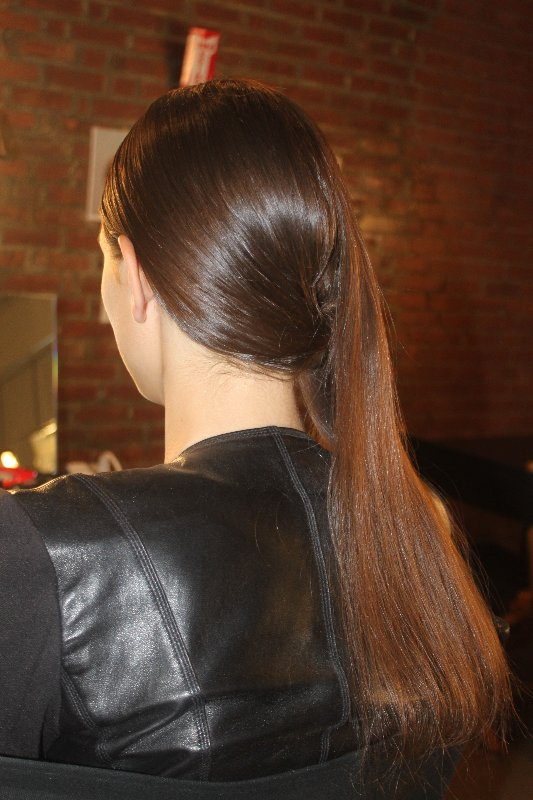 To achieve this look, stylists first created a side part in the front, and used Kiehl's Clean Hold Gel and Serge Normant Hair Spray for a high-gloss effect. In the back, hair was gathered into an off-centre bun, where a section of hair reserved from the side was used to cover and fill it in.