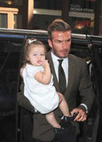Harper Beckham hitched a ride on David Beckham's hip while out celebrating her mom's successful runway show.