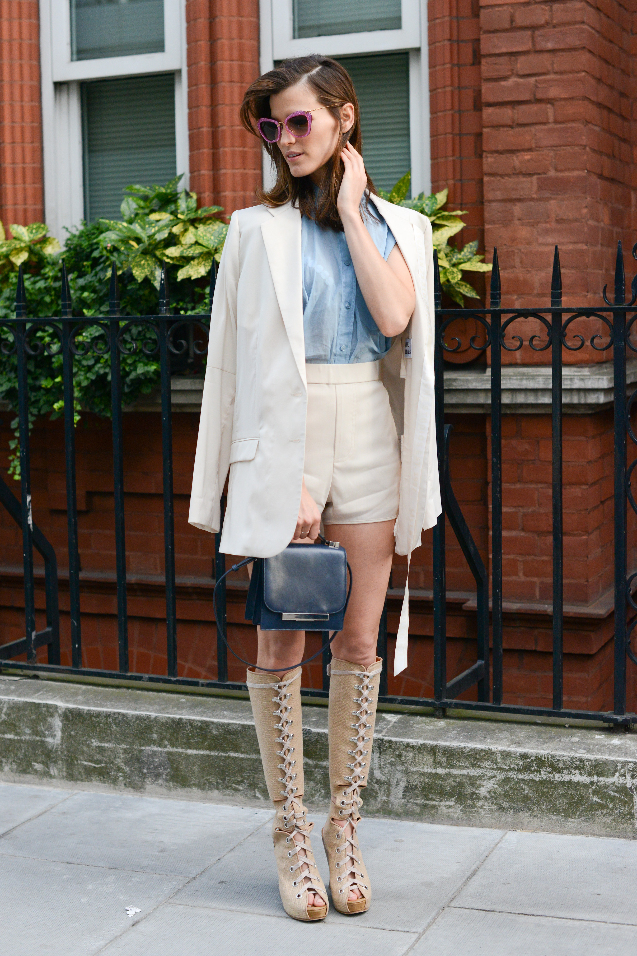 Hanneli Mustaparta donned a sweet ivory-hued short suit ensemble with killer lace-up boots and a navy blue The Row bag.