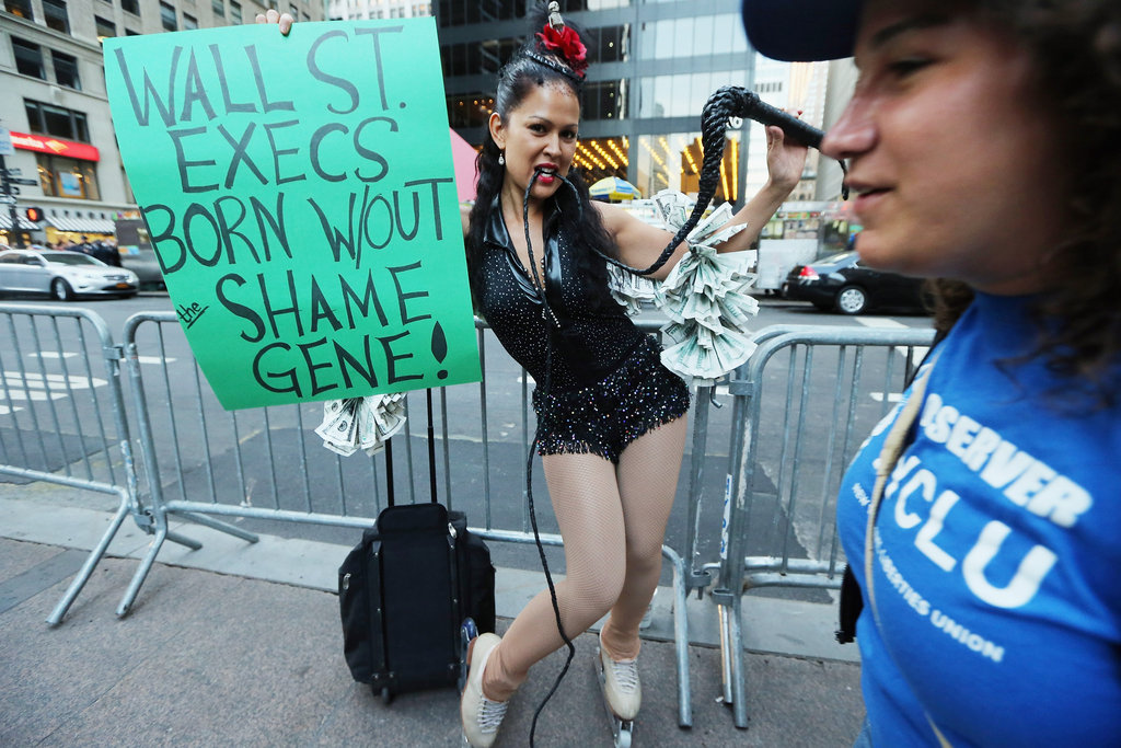 "A woman supported OWS in New York City's financial district with a sign that read ""Wall St. execs born without the shame gene!"""