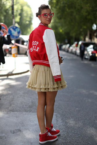 The letterman jacket gave this pleated mini a tomboy twist and furthered the playful pops of red in her look.