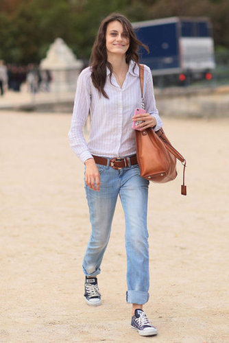 A tucked-in buttonup and slick bag offset the casual feel of a cuffed boyfriend jean-and-Converse combo.