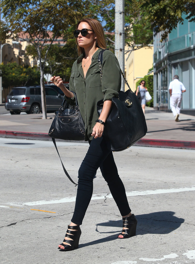 Lauren Conrad wore an army-green shirt with two black handbags.