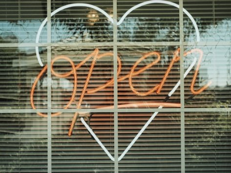 Neon 'Open' sign framed in a heart-shape in a window Photographic Print