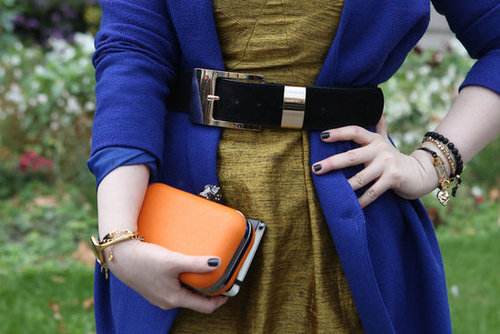 Colorblocking, complete with a pop of tangerine on her clutch.