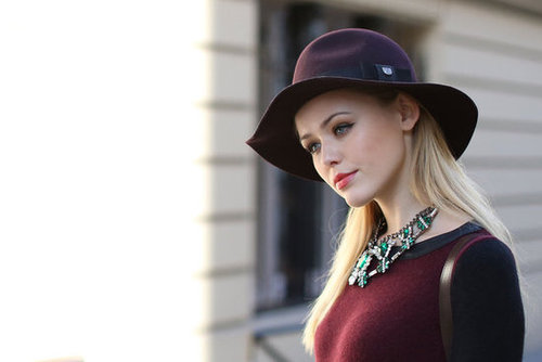 Emerald jewels contrasted the rich burgundy on her Fall fedora.