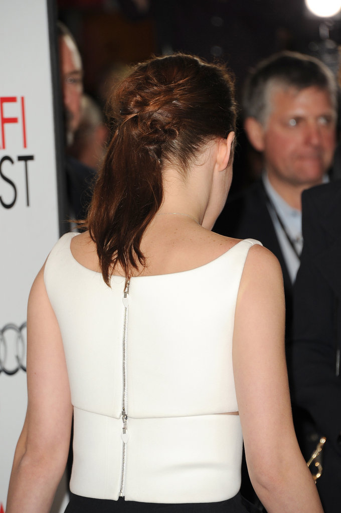 A closer glimpse of her top shows off that back zip and a knotted ponytail.