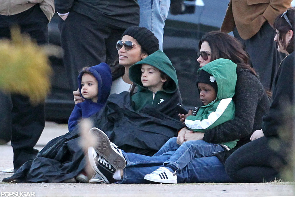Camila Alves held Levi McConaughey and Vida McConaghey in her lap next to Sandra Bullock and little Louis Bullock.