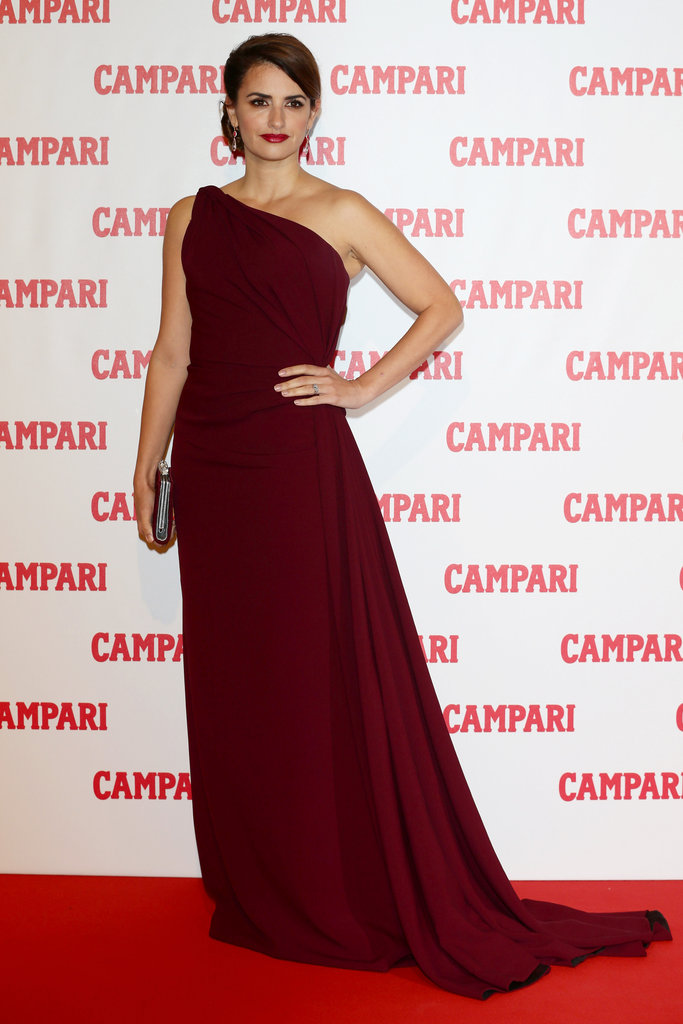 At the Campari Calendar unveiling party in Milan on November 13, Penelope Cruz — who is the star of the calendar this year — faced the media in a show-stopping oxblood-coloured gown.