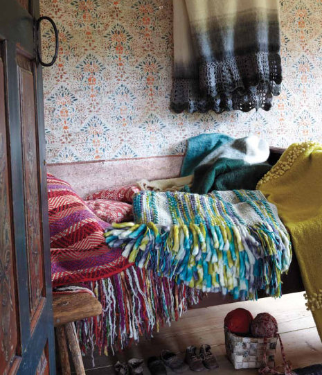 When it comes to bedding, go for an eclectic, cabin-inspired vibe. Think: more is more. Use a variety of throw blankets and accent pillows to bring out the colors in your wallpaper — and don't stress about matching the shades exactly.  Source: Anthropologie