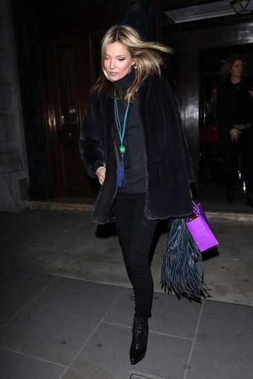 Kate Moss showed off her bohemian-rocker chic with a fur coat and a fringed bag in tow.
