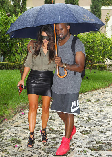 Kanye West held onto Kim Kardashian and an umbrella while they were out in Miami in October 2012.