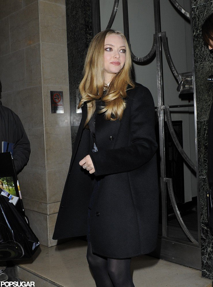Amanda Seyfried covered her dress with a black coat.