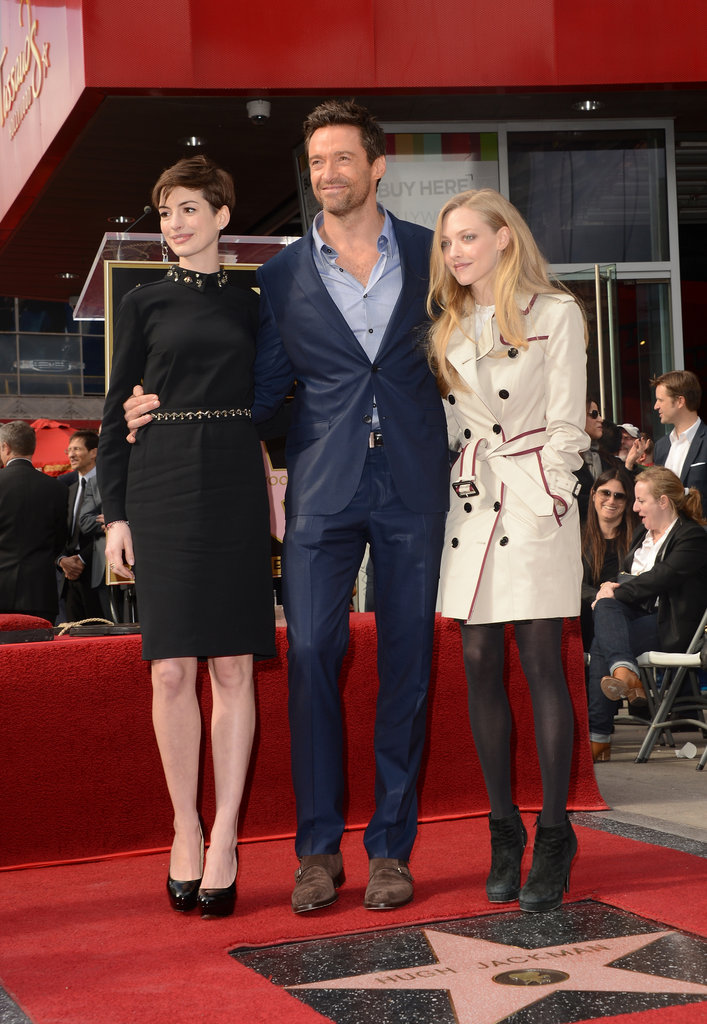 Anne Hathaway and Amanda Seyfried put their arms around Hugh Jackman.