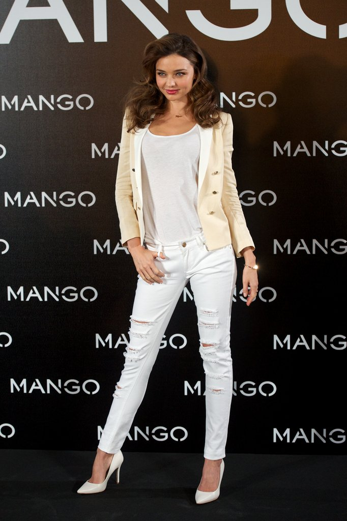 Miranda Kerr glammed up white denim with a tweedy jacket and pumps for her appearance as the new face of Mango in Madrid.
