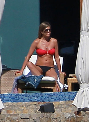 Jennifer Aniston worked on her tan in a mismatched two-piece — we love that she brightened up her black bottoms with a berry-hued top.